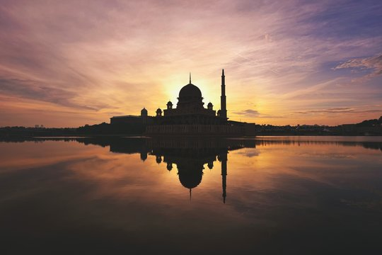 Silhouette Of Putra Mosque By River Against Sky During Sunset