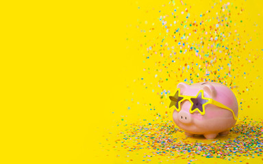 A pink piggy bank in fun glasses at a party. Yellow background.