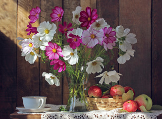 still life with flowers and apples.