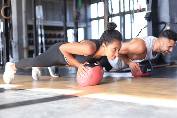 Beautiful young sports couple is working out with medicine ball in gym.