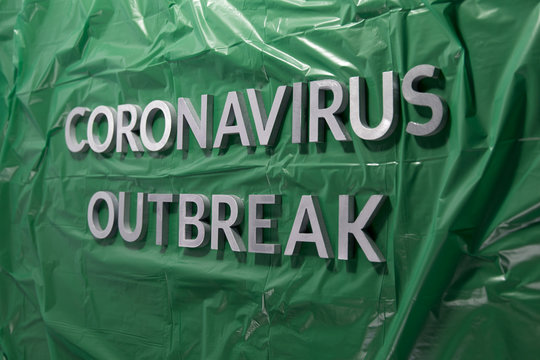 The words coronavirus outbreak laid with silver metal letters on green crumpled plastic film