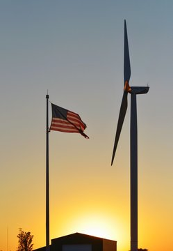 Low Angle View Of American Flag By Windmill During Sunset