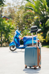 Blue SUITCASE with a hat on the handle, stands on the street, against a background of tropical palm trees and a scooter. The concept of vacation and travel in Thailand.