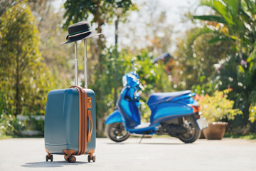 Blue SUITCASE with a hat outdoors on a background of tropical greenery and a scooter. The concept of vacation and travel in Thailand.