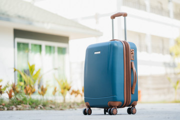 larger blue suitcase against the backdrop of the hotel lobby in the rays of sunlight. Vacation concept, summer travel.