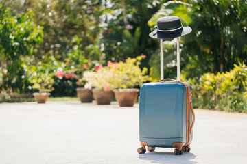 large suitcase stands on the street against a background of tropical greenery and palm trees. The concept of a summer vacation.