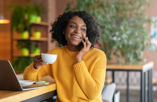 Positive afro girl having conversation with clients on phone