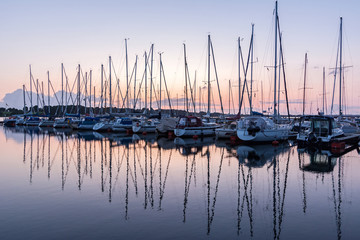 Sailing boats in the harbour reflecting in the water during beautiful sunset