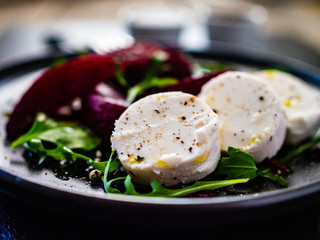 Beetroot salad with goat cheese on black stone plate