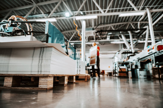 Low angle view of piles of sheets in printing shop. In background are worker and printing machines.