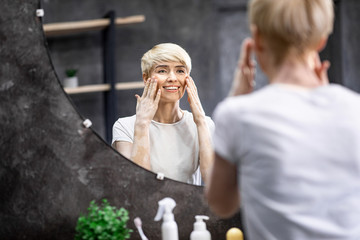 Lady Touching Face Skin Looking In Mirror In Bathroom
