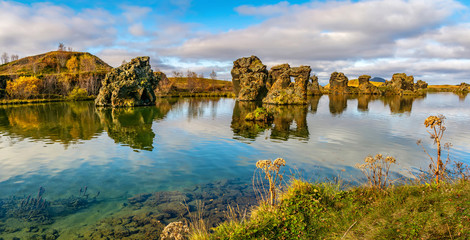 Amazing sunny day on lake Myvatn, Iceland, Europe. Volcanic rock formations reflected in the blue clear water of a volcanic lake. Artistic picture. Beauty world. Travel concept. Panorama