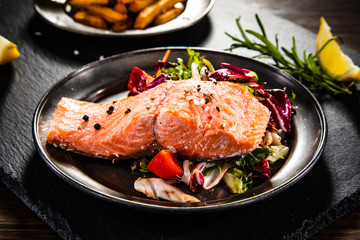 Roasted salmon with french fries and vegetable salad