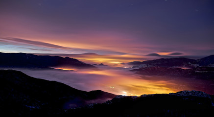 Amanecer entre nubes en lo alto de una montaña