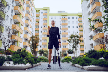 Fotomurales - Full length of attractive caucasian sportsman with artificial leg standing in park surrounded by buildings and eating banana.