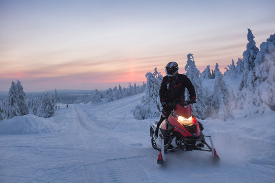 Man With Snowmobile On Field During Winter Against Sky