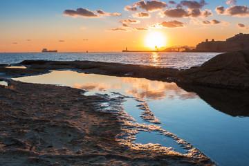 Rocky coastline of Malta and Mediterranean Sea at sunrise