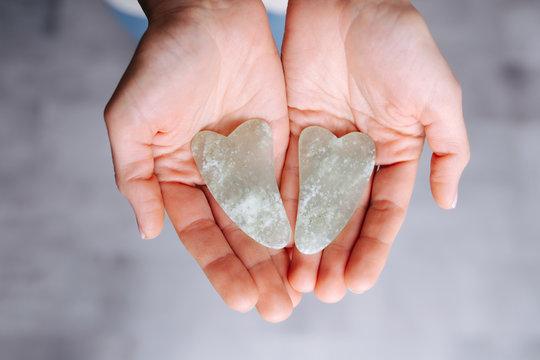Hands presenting gua sha stones over grey floor. Top view.