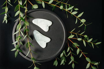 Gua sha stones on a plate with eucalyptus branches over black. Top view.