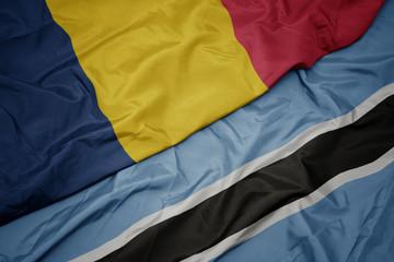 waving colorful flag of botswana and national flag of chad.