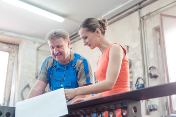 Metalworker and customer discussing plans