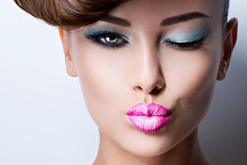 face of beautiful flirting woman with fashion bright eye makeup