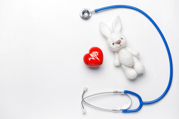 Stethoscope, heart and baby toy on light background