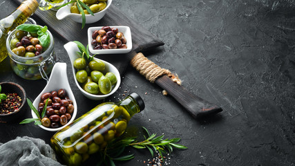 Wall Mural - Olives A set of colored olives on a black stone background. Top view. Free space for your text.