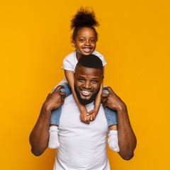 Cheerful portrait of black dad and daughter over yellow background