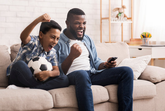 Black father and son soccer fans watching football on tv