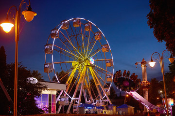 Foto auf Gartenposter Vergnugungspark Illuminated ferris wheel in amusement park at a night city