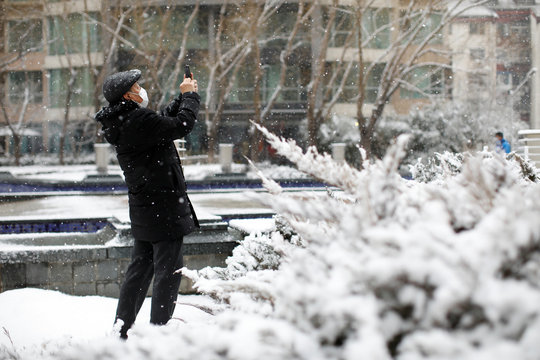 A man wearing a face mask takes photos with his cellphone during a snowfall at a residential complex, as the country is hit by an outbreak of the new coronavirus, in Beijing