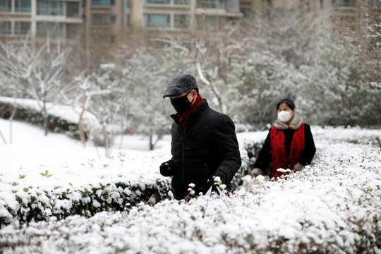 People wearing face masks walk at a residential complex during a snowfall, as the country is hit by an outbreak of the new coronavirus, in Beijin