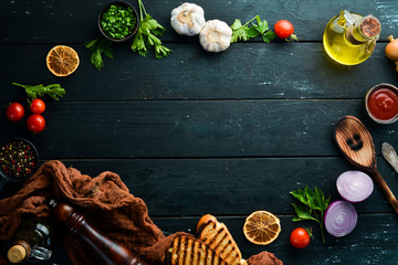 Fototapete - Black food background. Vegetables and spices on black background. Top view. Free space for your text.