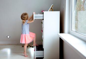 Young girl child climbing on modern high dresser furniture, danger of dresser dipping over concept....