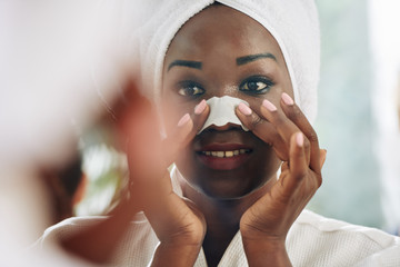 Horizontal close up portrait shot of attractive young woman standing in front of mirror applying pore strip on her nose