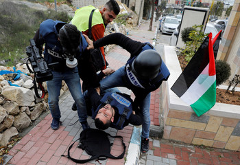 Wounded Palestinian photojournalist is evacuated during an anti-Israel protest against the U.S. President Donald Trump's Middle East peace plan, in Hebron in the Israeli-occupied