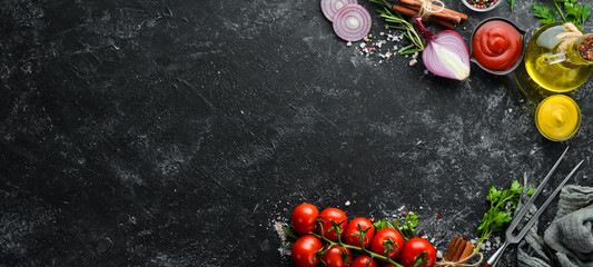 Wall Mural - Black stone cooking background. Spices and vegetables. Top view. Free space for your text.