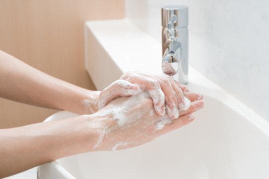 Asian woman washing hands  in a sink
