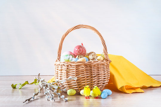 Easter holiday still life. Wicker basket with easter eggs, yellow napkin and bouquet of willow on sunlight