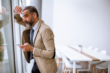 Senior businessman using mobile phone in modern office