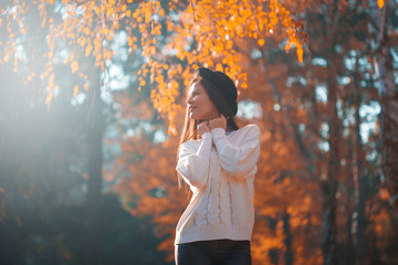 Woman in white jumper, black hat, autumn nature, happy