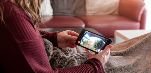 Brilon, North Rhine Westphalia / Germany - January 31st 2020: A woman is lying on the couch. She looks at cell phone. Display shows shot of the surveillance camera ring from Amazon.....