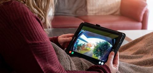 Brilon, North Rhine Westphalia / Germany - January 31st 2020: A woman is lying on the couch. She looks on tablet. Display shows shot of the surveillance camera ring from Amazon.