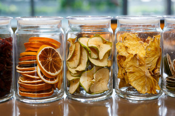 Dried oranges and apples in glass jars.