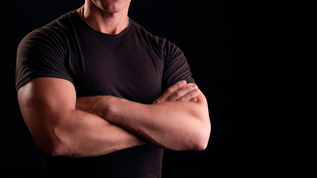 A man with strong arms. Male security guard in a black t-shirt. Strong man on a black background. Concept male security guard.