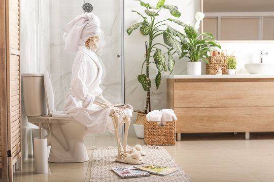 Skeleton in bathrobe with mobile phone sitting on toilet bowl