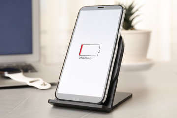 Mobile phone charging with wireless device on light grey stone table
