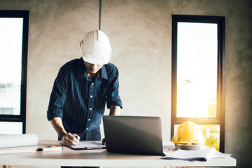 engineer working on blue print and search on laptop in construction site