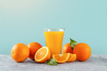 Fresh orange juice glass and oranges on blue background